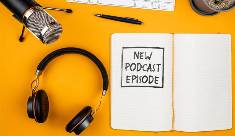 A picture of a notepad on desk with text New Podcast Episode