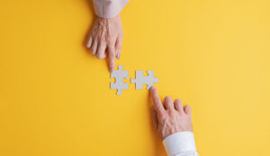 A photo of people pushing puzzle pieces together