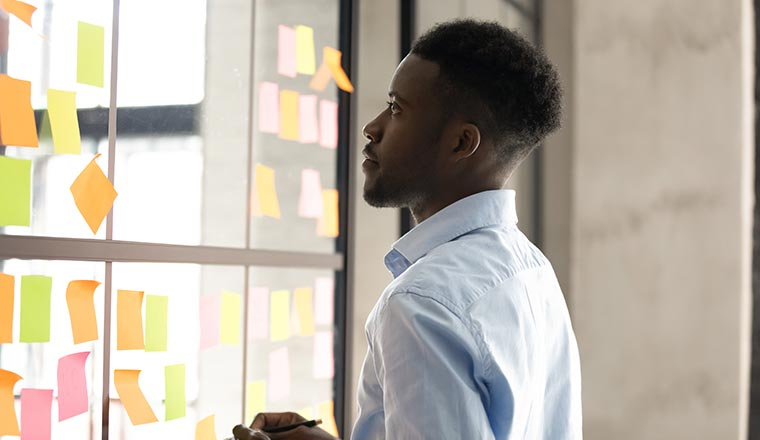 A photo of a man staring at a post-it board