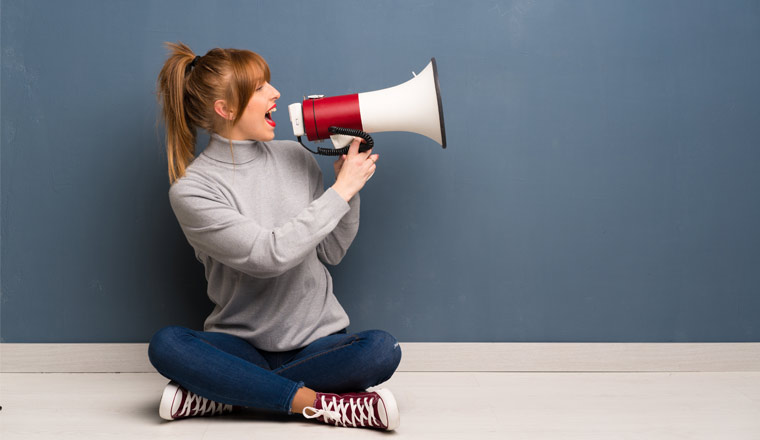 A picture of a girl shouting down a megaphone