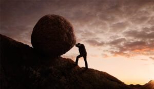 A picture of a person pushing a large rock up a hill