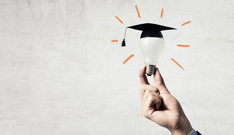 A photo of a light bulb with a graduation hat