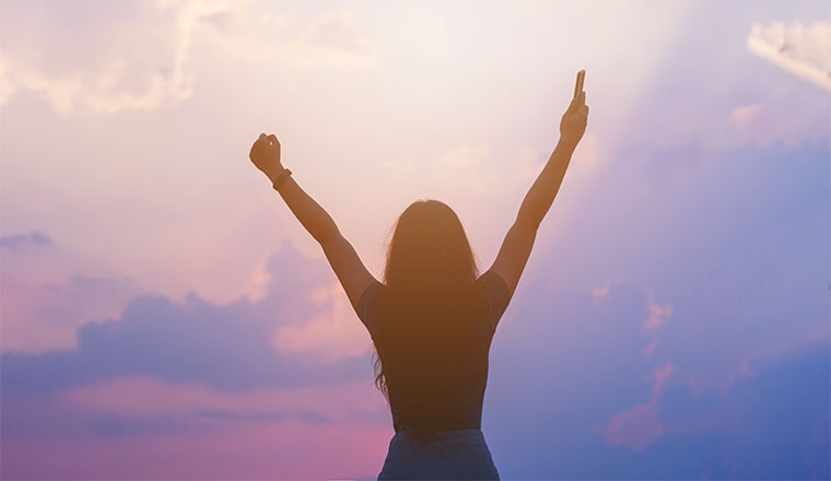 A photo of someone with there hands-up with joy