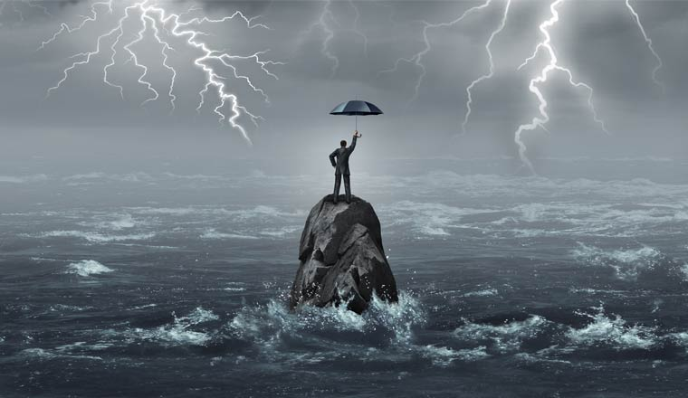 A picture of an agent stood on a rock out at sea in a storm holding an umbrella