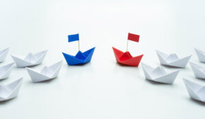 A picture of blue and red paper ship leading a team of white ships
