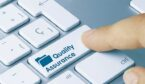 """A photo of someone pressing a button that says """"quality assurance"""""""