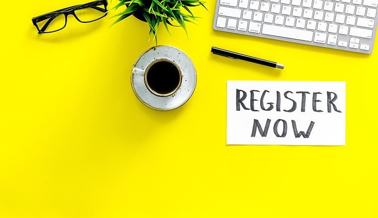 """A photo of a desk saying """"register now"""""""
