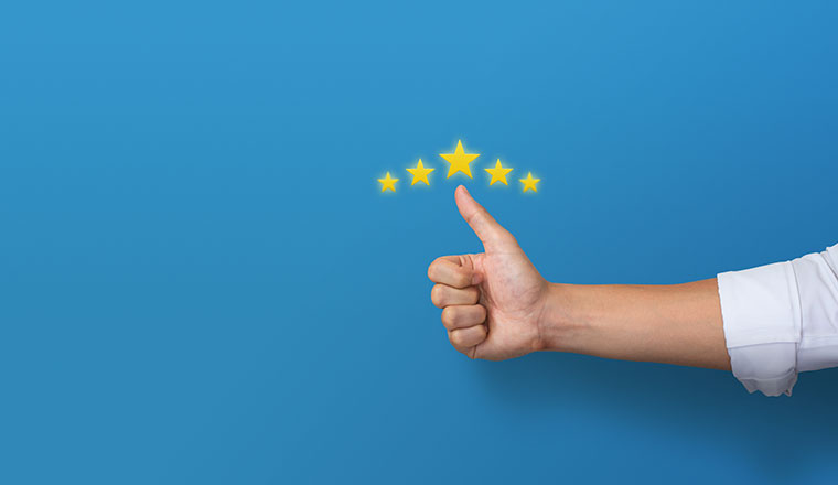 A photo of someone with their thumb up and stars around it