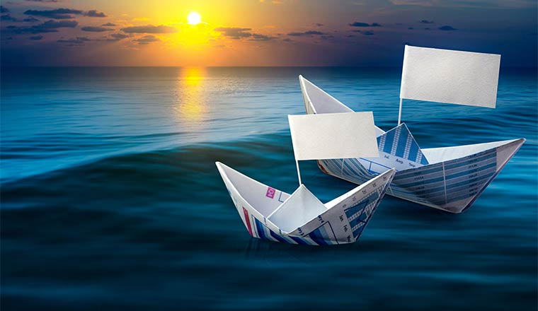 A photo of two paper boats next to each other