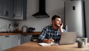 A picture of an agent working at home on kitchen table with laptop