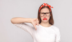 A picture of a lady frowning with her thumb pointing down