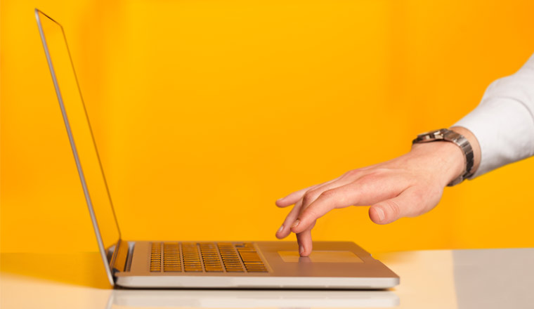A picture of a laptop and hand on keyboard
