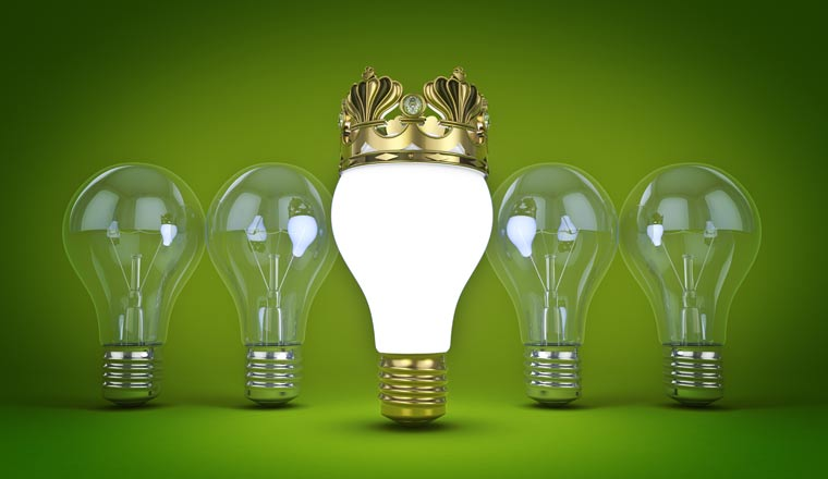 A picture of an illuminated lightbulb with a golden crown in front of four lightbulbs