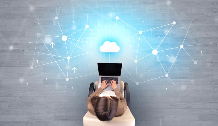 A picture of a woman on a laptop with cloud data