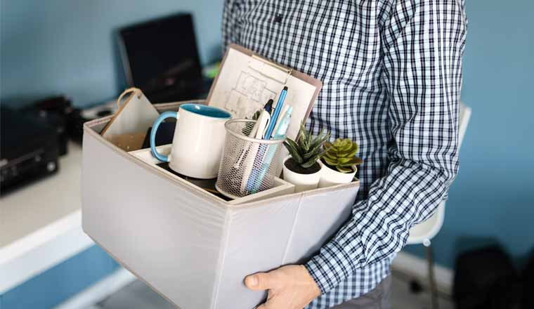 A picture of an employee with a box of belongings