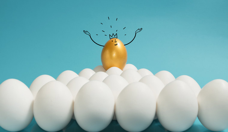 A picture of a golden egg wearing standing above a group of white eggs