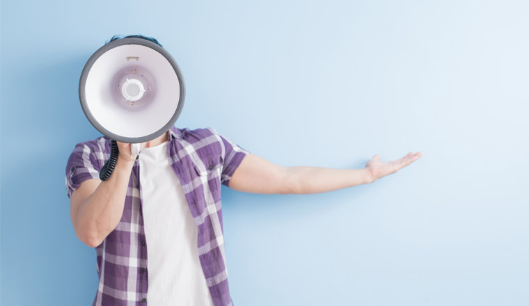 A picture of a person gesturing whilst using a megaphone