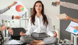 A picture of an agent sat on her desk meditating