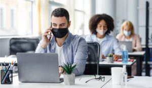 A picture of office workers wearing masks and socially distanced