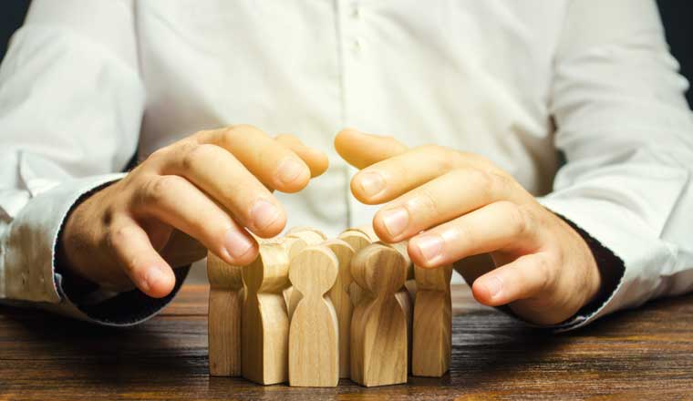 A picture of a pair of hands shielding a group of wooden figurines
