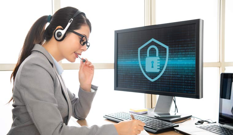 A picture of a person in a headset sat in front of a screen showing a padlock