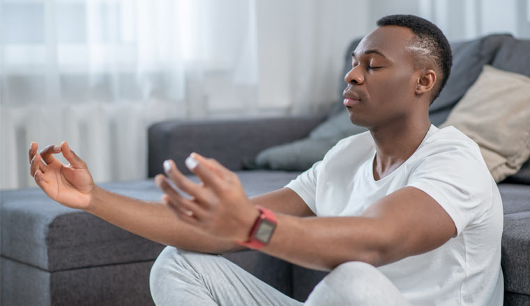 A picture of a person in white clothes meditating and looking peaceful
