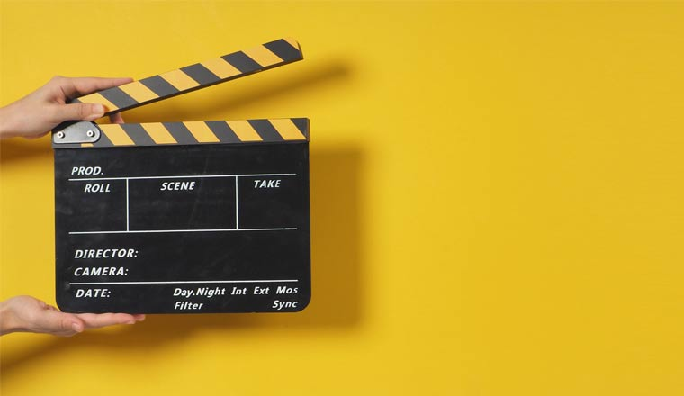 Hand is holding clapper board or movie slate on yellow background