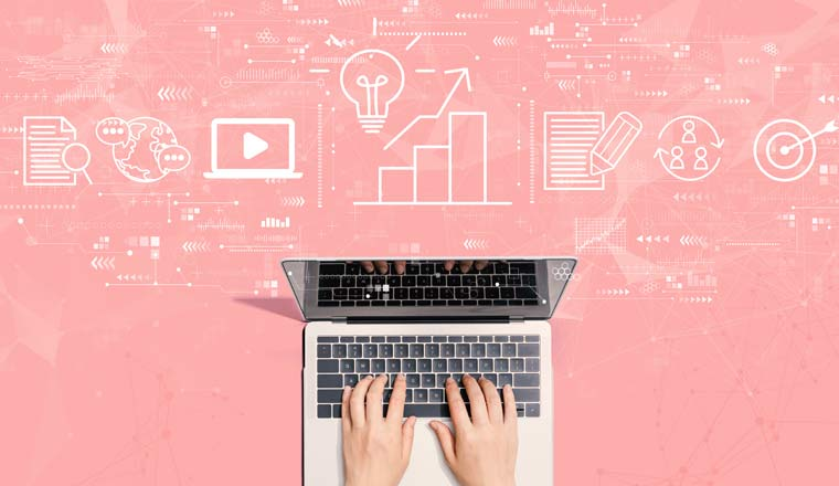 A laptop on a pink background with business icons above it