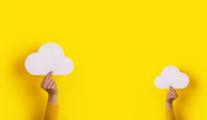 Two hands holding paper cloud over yellow background