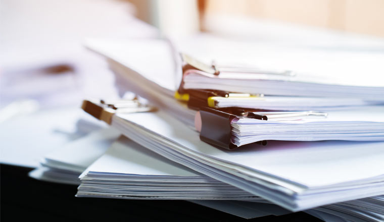A stack of paper documents with clip papers on table