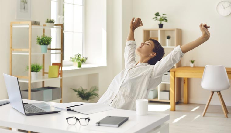 A person sitting at an office desk stretching
