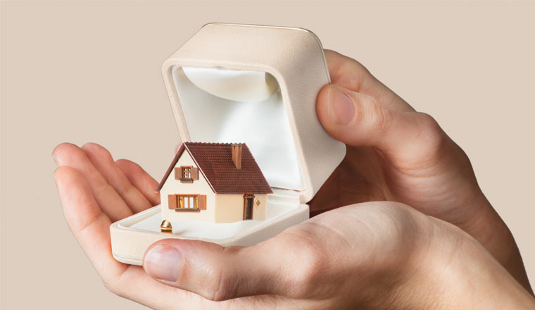 A a pair of hands holding a house inside a ring box