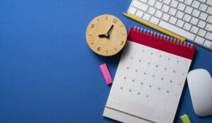close up of calendar, alarm clock and accessories on the blue table background