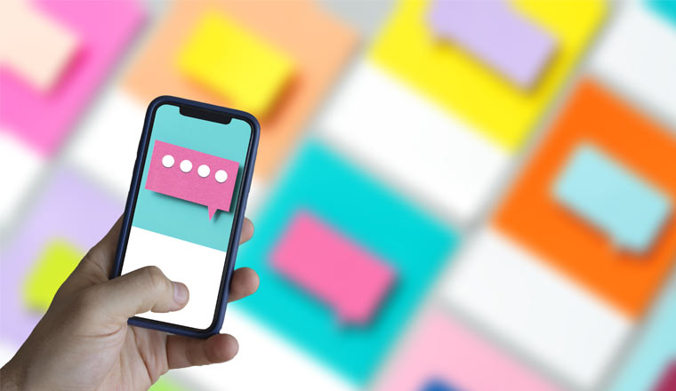 Hand typing text on smartphone with speech bubbles