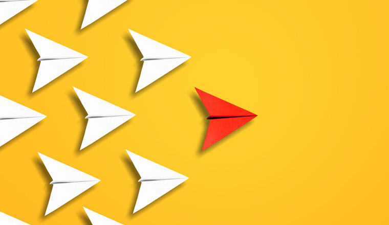 A red paper aeroplane leading a group of white ones on a yellow background
