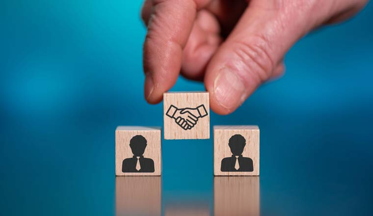 A picture of a hand placing a wooden block showing a handshake inbetween two blocks with people on them