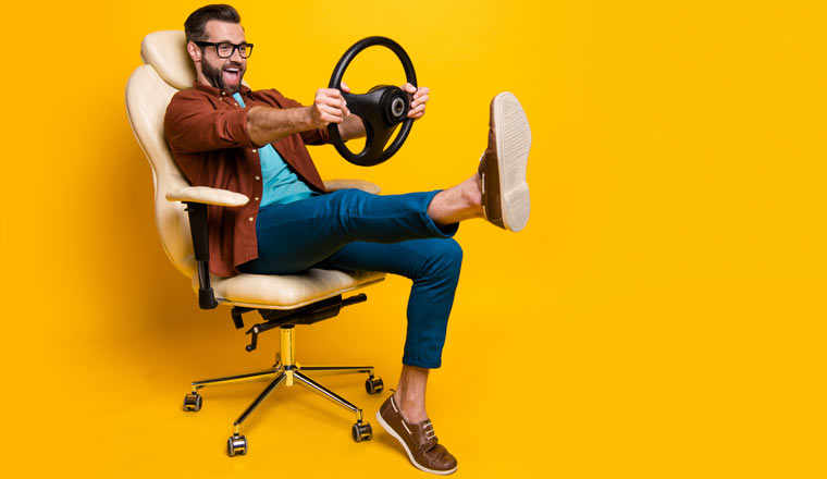 Happy person in a chair holding a steering wheel