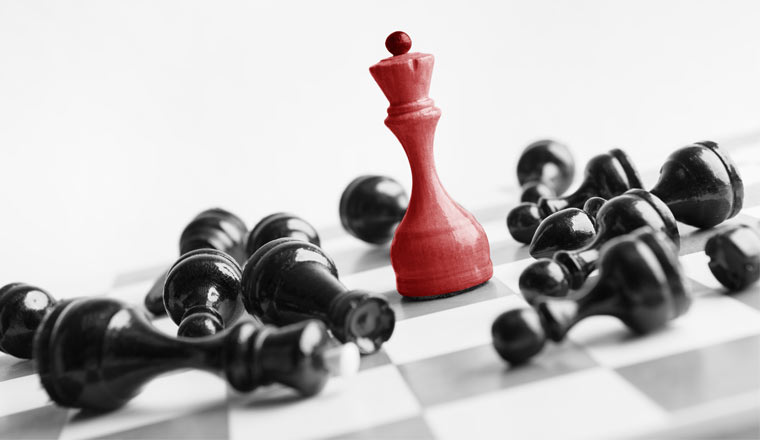 Red chess queen beats blacks on chessboard