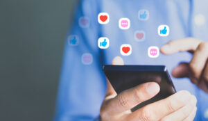 Person using a mobile phone social media like icons