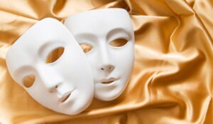Theatre concept with the white plastic masks on gold fabric