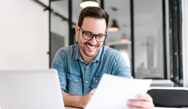 A person smiling looking at paperwork