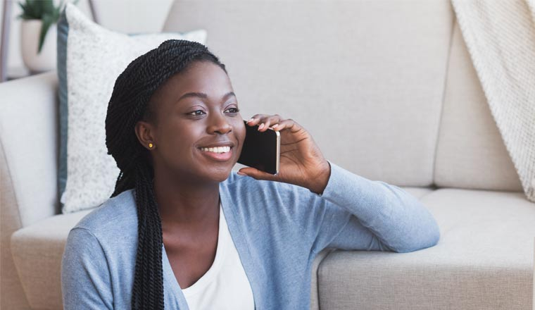 Person on mobile phone sat in front of a sofa