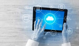 Hand touching tablet with cloud computing and online icons