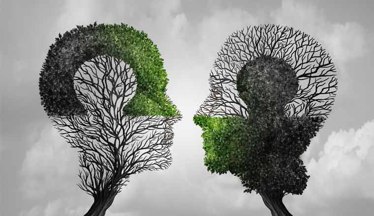 An image of two heads shaped out of trees with puzzle markings in the leaves