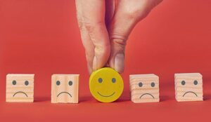 Customer showing rating with happy icon on yellow smiley face in the middle of four sad faces on blocks