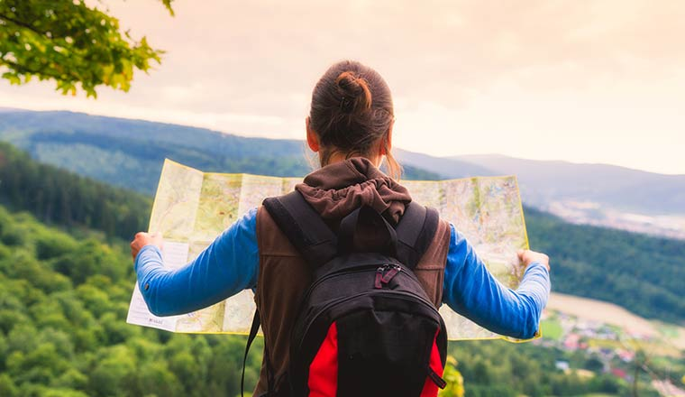 Traveler with backpack checks map to find directions in wilderness area