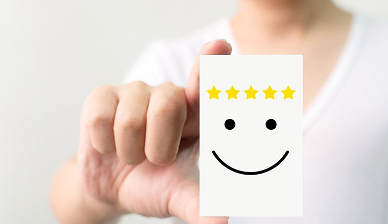 Person holding card with smiley face and five stars