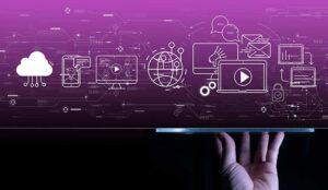 Hand using a digital tablet computer on dark violet background