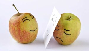 A happy apple facing a sad apple hidden behind a smiling face on paper