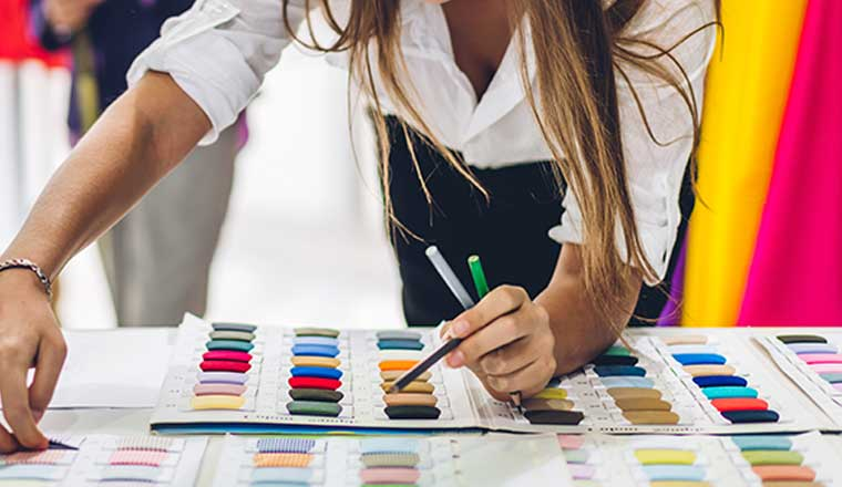 A fashion designer stylish stand and working with color textile samples